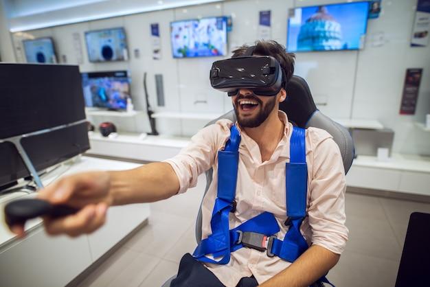 Lachende bebaarde man met de draadloze joystick in de hand tijdens het testen van de vr-bril in een tech store.