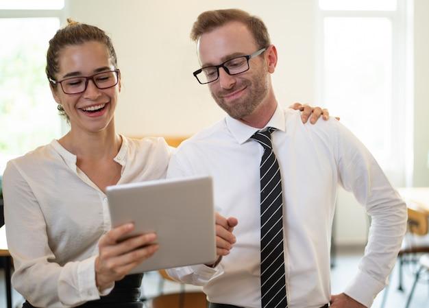 Lachende bedrijfsmensen die op iets op tabletcomputer letten.