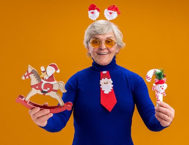 Lachende bejaarde vrouw in zonnebril met santa hoofdband en santa stropdas santa bedrijf op hobbelpaard decoratie en riet van het suikergoed geïsoleerd op een oranje achtergrond met kopie ruimte