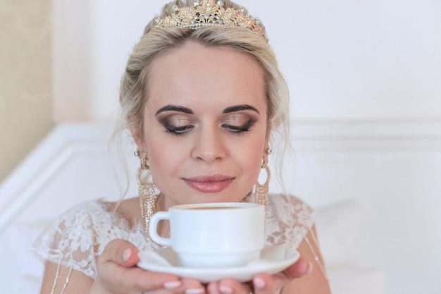 Lachende blonde bruid in een hotelkamer koffie drinken