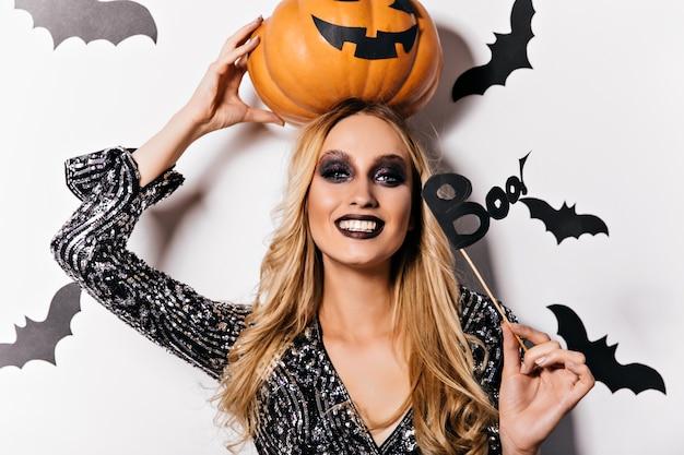 Lachende blonde heks poseren met vleermuizen op muur. prachtige jonge tovenaar die grote oranje pompoen houdt.