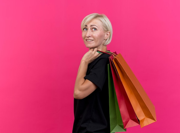 Lachende blonde slavische vrouw van middelbare leeftijd permanent in profiel te bekijken met boodschappentassen op schouder kijken kant geïsoleerd op karmozijnrode achtergrond met kopie ruimte