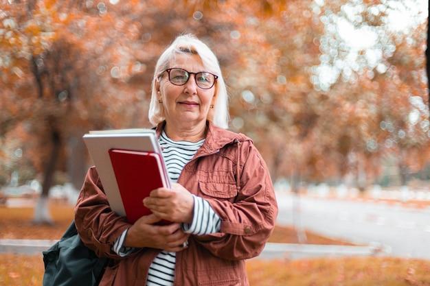 Lachende blonde vrouw in casual kleding staat met notitieboekjes en rugzak kijken naar de camera wandelen in het najaar park