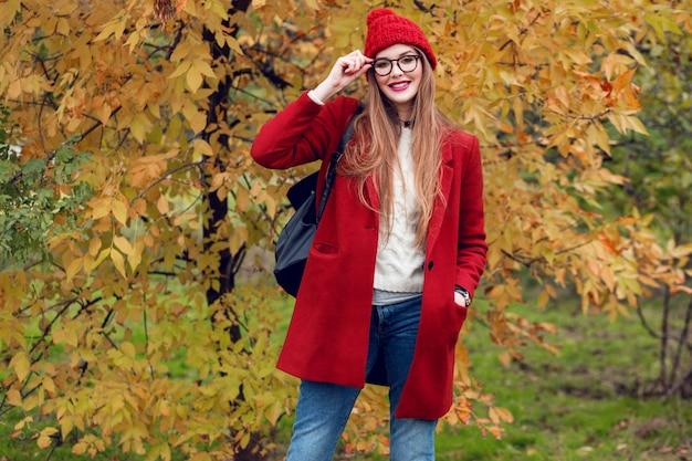 Lachende blonde vrouw met lange haren wandelen in zonnige herfst park in trendy casual outfit.