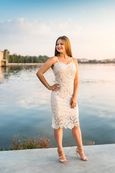Lachende blonde vrouw poseren in mode jurk op strand