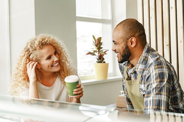 Lachende blonde vrouw praten met een ober van een koffieshop aan de balie tafel