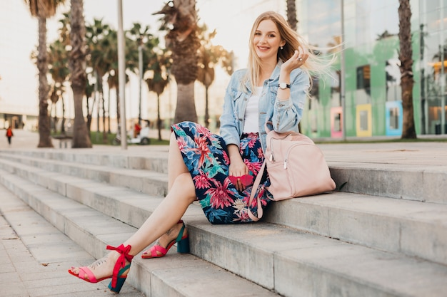 Lachende blonde vrouw zittend op de trap in de stad straat in stijlvolle bedrukte rok en oversized denim jasje met lederen backpac