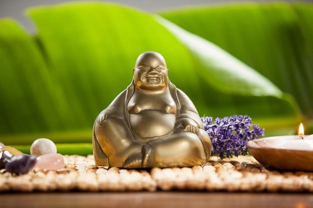 Lachende boeddha beeldje, aangestoken kaarsen en kiezels stenen