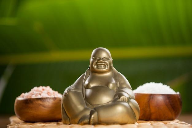 Lachende boeddha beeldje en zeezout in houten kom
