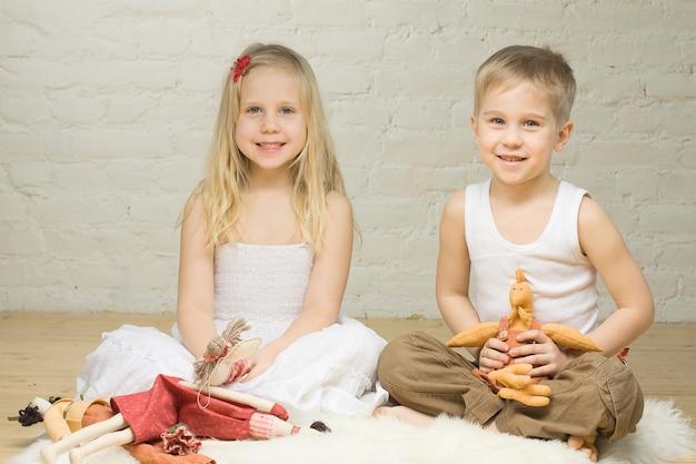 Lachende broers en zussen kinderen spelen met opgezette dieren