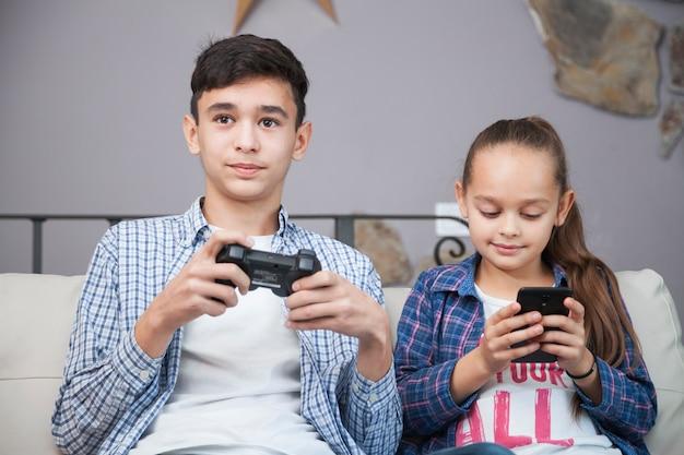 Lachende broers en zussen met smartphone en controller