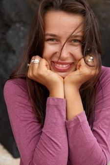Lachende brunette blanke vrouw houdt beide handen onder de kin, drukt positieve emoties uit