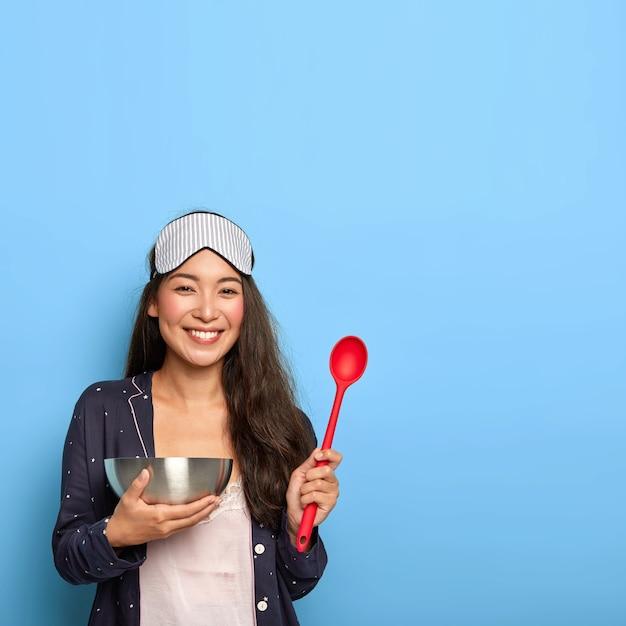 Lachende brunette gemengd ras vrouw houdt lepel en kom, blij om te proberen nieuw recept van heerlijk gerecht, draagt slaapmasker en slaappak, maakt gezond ontbijt