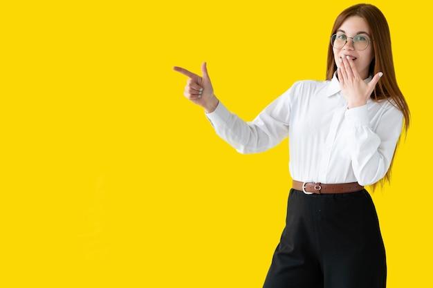 Lachende brunette in een overhemd, kijkend en wijzende vinger op een gele muur