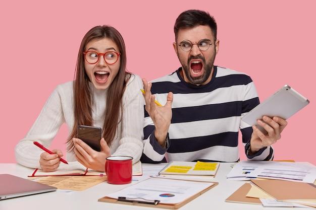 Lachende brunette vrouw houdt cellulaire, schrijft notities in dagboek, geërgerd bebaarde man gebruikt moderne touchpad