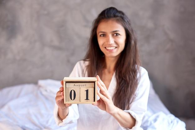 Lachende brunette vrouw houdt houten eeuwigdurende kalender vast met 1 augustus datum vorige maand van de zomer