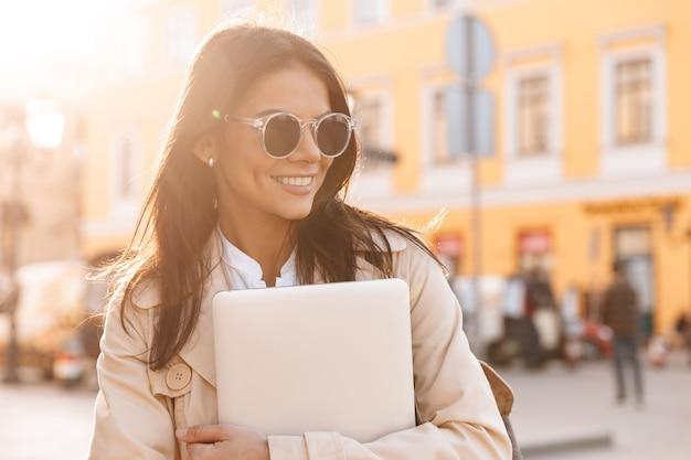Lachende brunette vrouw in jas en zonnebril knuffelen laptopcomputer