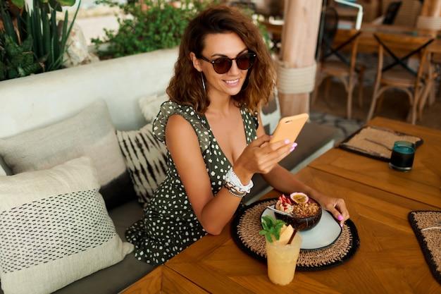 Lachende brunette vrouw in stijlvolle jurk praten via de mobiele telefoon in tropische café in de buurt van strand.