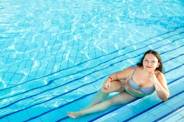 Lachende brunette vrouw ligt in het zwembad. horizontale foto
