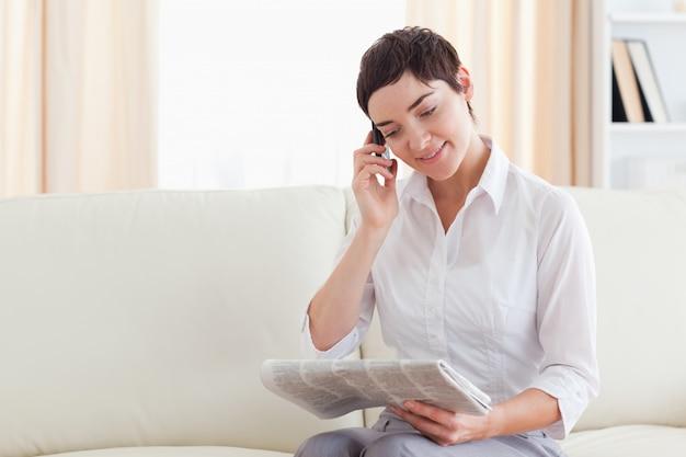 Lachende brunette vrouw met een mobiele telefoon en een krant