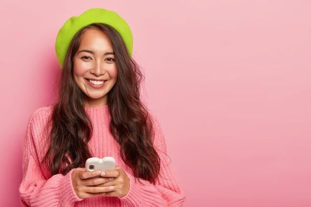 Lachende brunette vrouw met lang haar, draagt felgroene baret en oversized trui, bezit moderne mobiele telefoon, verbonden met draadloos internet