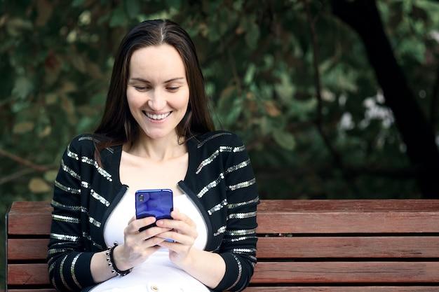 Lachende brunette vrouw met smartphone in haar handen zit texting op bankje in zomer park, communicatieconcept