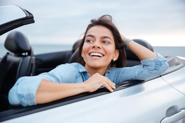 Lachende brunette vrouw rusten in haar cabriolet geparkeerd op het strand