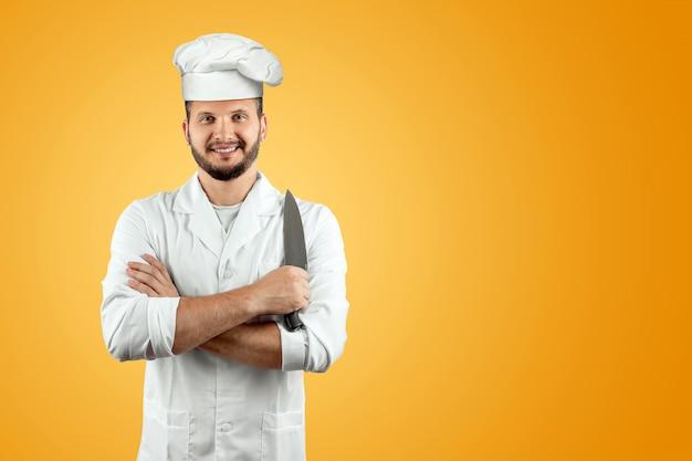 Lachende chef-kok in een hoed met een mes op een oranje achtergrond