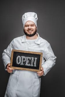 Lachende chef-kok met open schrijven
