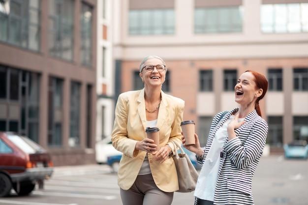 Lachende collega's. twee elegante knappe blanke collega's die lachen terwijl ze buiten staan met papieren kopjes koffie