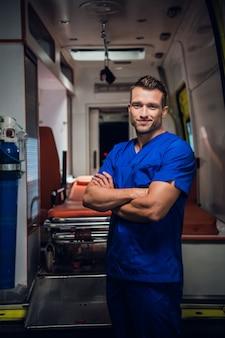 Lachende corpsman in een medisch uniform staat met een ambulance auto