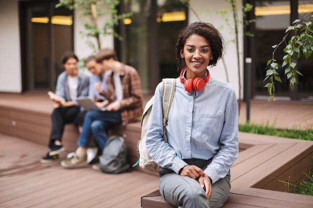 Lachende dame in shirt zittend op een bankje met rode koptelefoon en rugzak op de binnenplaats van de universiteit