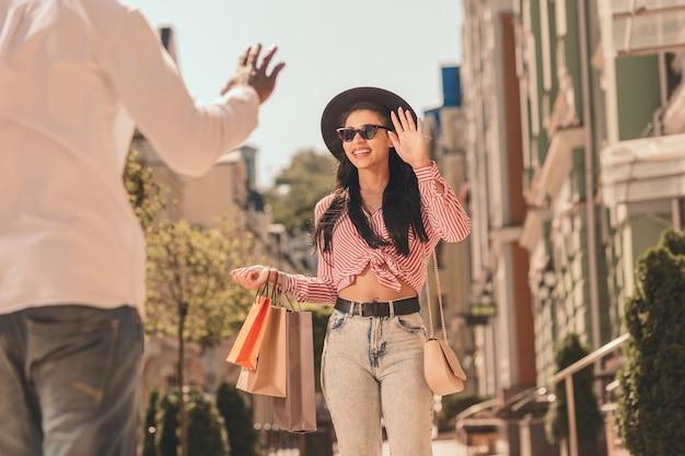Lachende dame met boodschappentassen zwaaiend naar een man op straat