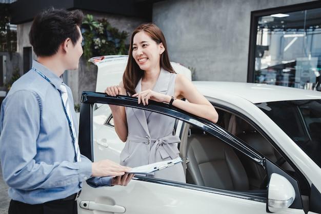 Lachende dame om de nieuwe auto op te halen bij de dealer.