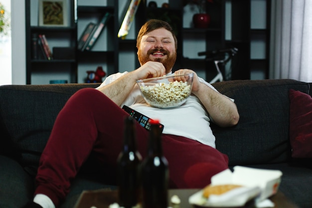 Lachende dikke man zit op de bank, eet pop-maïs en kijkt tv