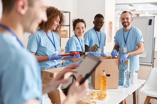 Lachende diverse vrijwilligers die levensmiddelen sorteren in kartonnen dozen die aan een donatieproject werken