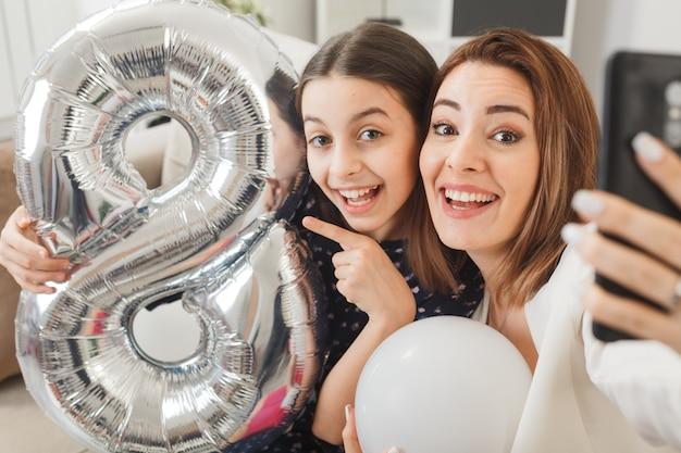 Lachende dochter en moeder met nummer acht ballon op gelukkige vrouwendag zittend op de bank nemen een selfie in de woonkamer
