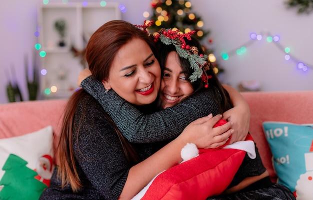 Lachende dochter en moeder omhelzen elkaar zittend op de bank en genieten van kersttijd thuis