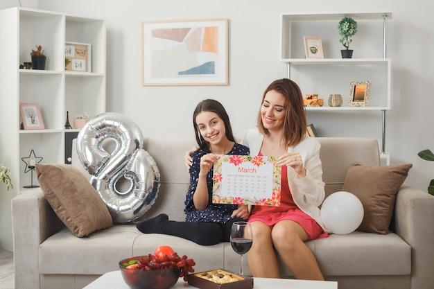 Lachende dochter en moeder op gelukkige vrouwendag met ansichtkaart zittend op de bank in de woonkamer