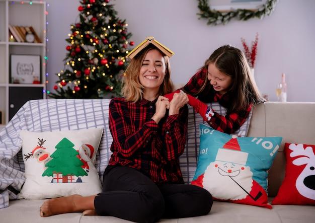 Lachende dochter speelt met haar moeder boek op hoofd zittend op de bank te houden en thuis te genieten van kersttijd