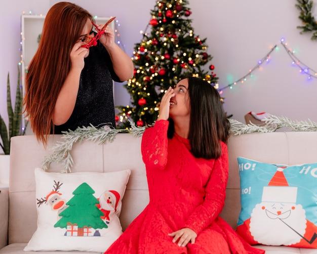 Lachende dochter zittend op de bank kijkt naar haar moeder in rendieren glazen genieten van kersttijd thuis
