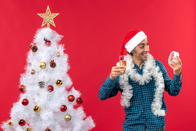 Lachende emotionele jonge man met kerstman hoed en met een glas wijn en lokking op de klok in de buurt van de kerstboom op rood