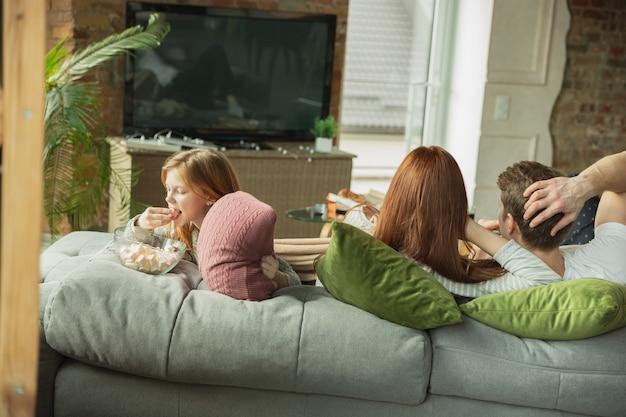Lachende familie die thuis leuke tijd samen doorbrengt, ziet er gelukkig en vrolijk uit