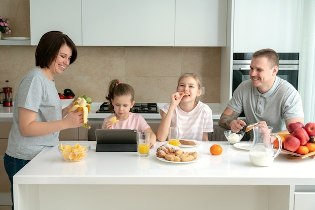 Lachende familie samen dineren aan de keukentafel en plezier, ouders met twee dochters
