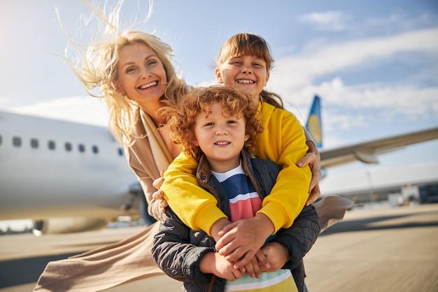 Lachende familie staat buiten het vliegtuig
