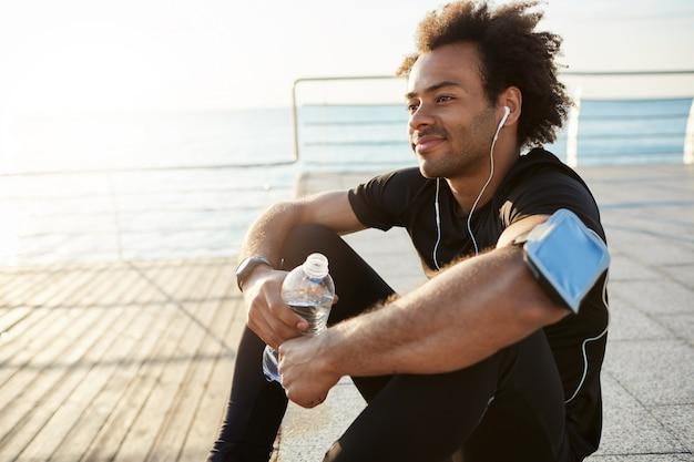 Lachende fitte donkere man atleet met borstelig haar drinkwater uit plastic fles na hard hardlopen aan zee. schot van mannelijke agent in zwarte bovenkant en beenkappen die na succesvol rusten