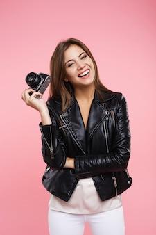 Lachende fotograaf die oud-filmcamera houdt kijkend recht met glimlach