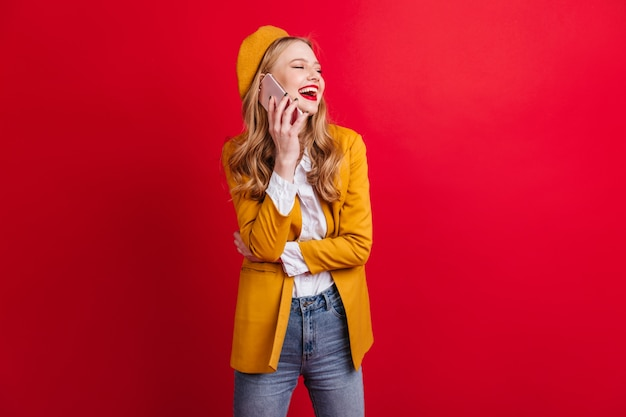 Lachende franse jonge vrouw praten over de telefoon. schattig blond meisje met smartphone geïsoleerd op rode muur.
