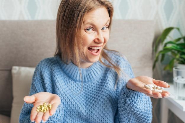 Lachende gekke vrouw met twee verschillende soorten pillen in haar handen op bed thuis.
