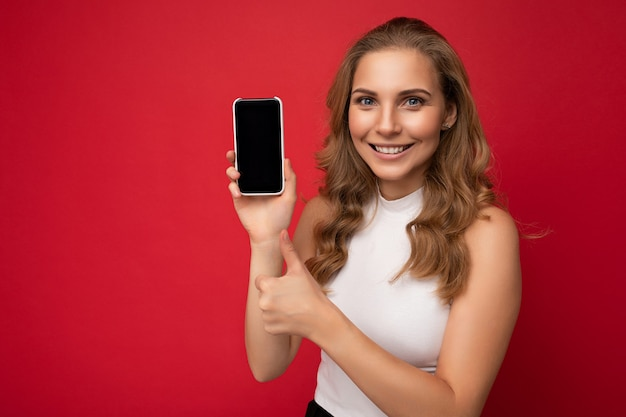 Lachende gelukkig mooie jonge blonde vrouw, gekleed in witte t-shirt geïsoleerd op rood oppervlak
